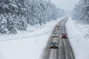 Nach dem Auto-Wintercheck – Autos auf einer verschneiten Straße durch den Wald