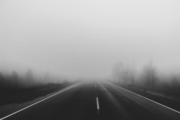 Nebelige Landstraße beim Autofahren im Herbst