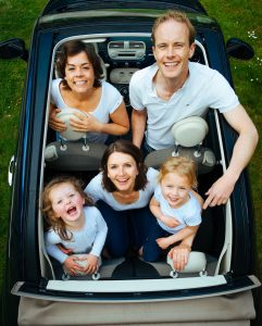 Familie im Auto beim Roadtrip in den Sommerurlaub