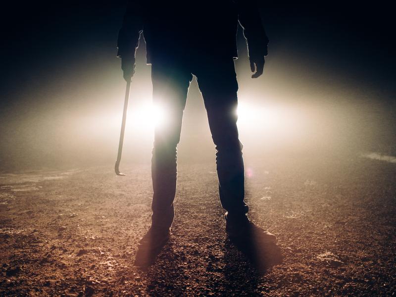 Mörder mit Waffe vor Autoscheinwerfern